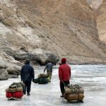 Porters pull their sledges laden with camping equipment on ice on the Chadar Trek in Ladakh