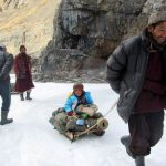 A Zanskari takes his little son on a joyride on the Chadar in Ladakh, Zanskar