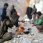 Porters warm their sleeping bags by the fire on the Chadar Trek in Ladakh