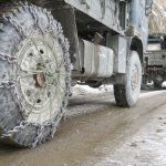 Army vehicles with snow chains to increase traction on icy roads during chadar trek in Ladakh